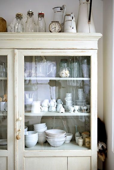 Farmhouse eclectic. Notice groupings of 3, stacking, and monochromatic color scheme