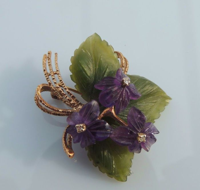 Broche / hanger boeket gemaakt van Amethist bloemen met blaadjes van jade en 3 diamanten gemaakt van 585 goud / 14 kt rond 1950  Mooie oude broche/hanger 'bloemboeket' met 3 kleine ruitjes paarse Amethist bladeren en Smaragd-groene jade bladeren gemaakt van 14 kt / 585 geel goudVoor verkoop een getuigenis van prachtige kunst door een goudsmid is: broche gemaakt van massief 14 kt / 585 goud.De gouden berg heeft een paarse bloem gemaakt van edelstenen.3 fijn gesneden bladeren gemaakt van…