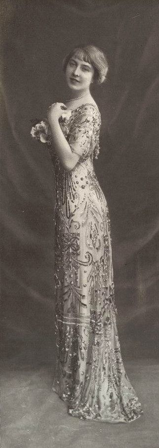 Les Modes (Paris) January 1911 robe du soir par Rivain & Co. robe du soir, en mousseline de soie améthyste garnie de paillettes et perles sur un fond orchidée.