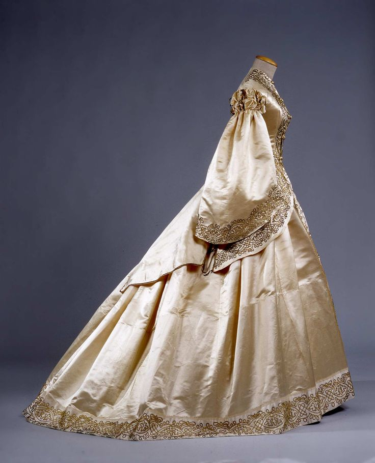 Circa 1862 Wedding dress three-piece (bodice, jacket, skirt) in ivory silk satin with application of two types of spikelets wire golden drawings of knots inspired by the Renaissance.  Via Galleria del Costume di Palazzo Pitti.