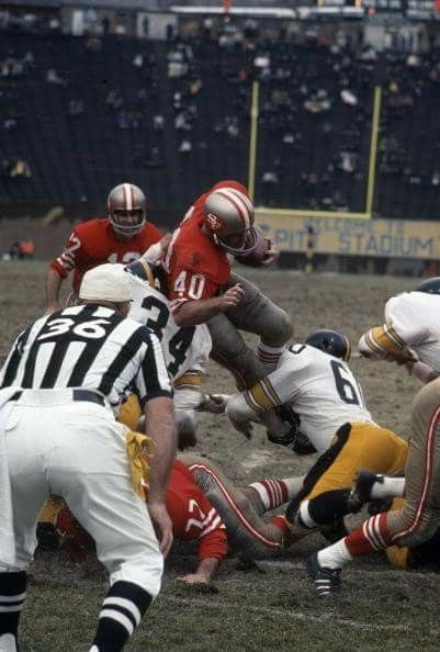 A 49er dives over some Steelers, 1960's.