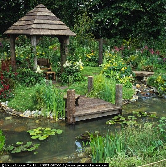 Rustic summerhouse enc. in astilbe, primula & bay willow herb leads to wooden jetty above pool skirted by iris, reeds & pickerel weed fed by tumbling stream