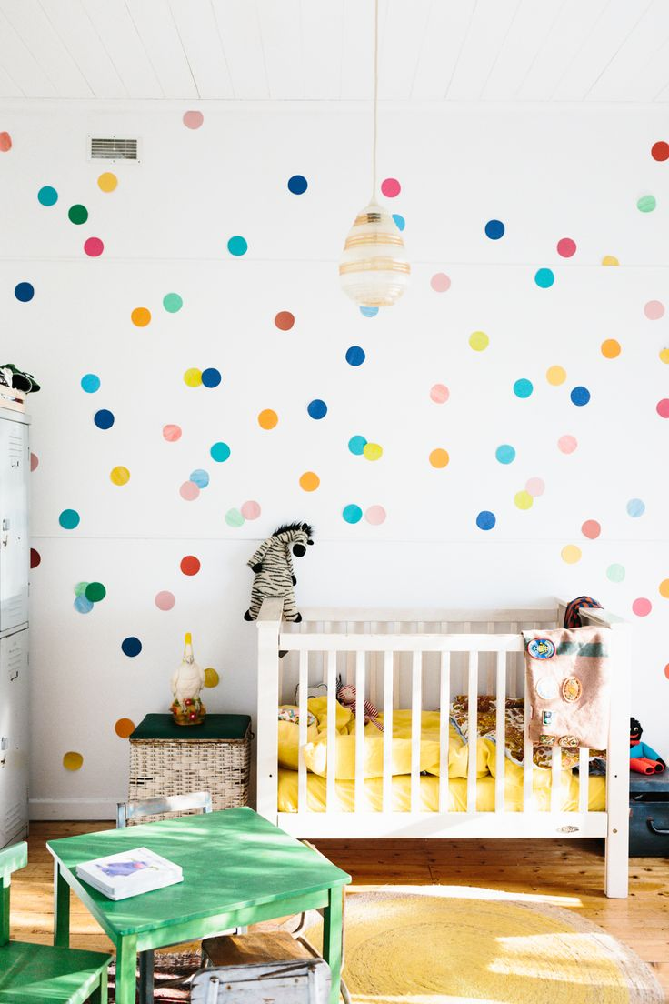 What a cute nursery. Colorful dots on te walls