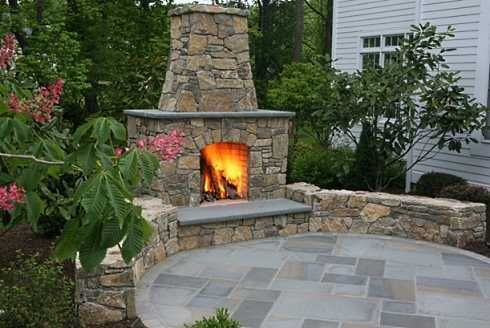 Patio with outdoor fireplace. Natural stone around the fire and also on the seat wall compliments the bluestone patio. Nice circular design.
