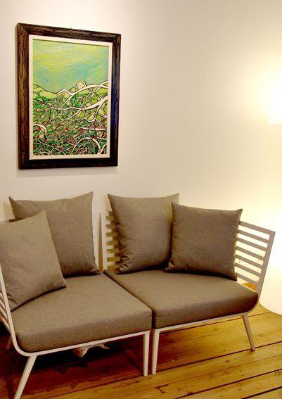 Anche con poco spazio si può dar vita ad un angolo caldo e accogliente: l'essenzialità delle linee di un divanetto modulare Gloster Furniture contrastano piacevolmente con le sinuosità del dipinto. Le tonalità del marrone, del verde, del grigio creano un contesto piacevole e armonico.