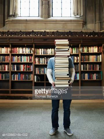 Stock Photo : Young man carrying stack of books in university library