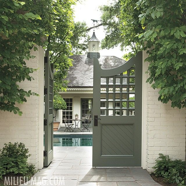 Latticework-patterned wooden gates, which open to a pool and pool house, convey…