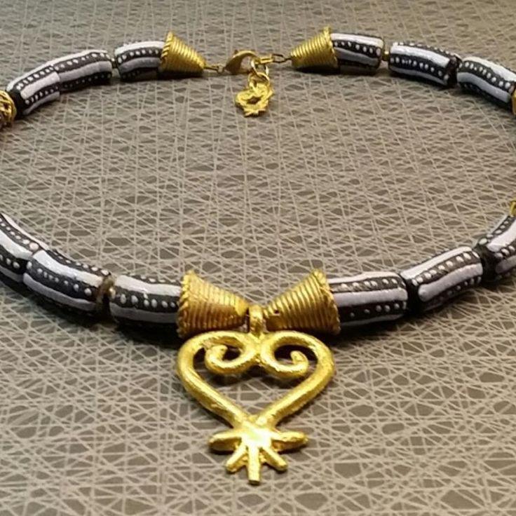 """Så ljuvligt halsband, ca 52 cm inkl. förlängning. Handgjorda och handmålade pärlor av återvunnet glas och mässing. Hänget är en Adinkra symbol """"Sankofa - Lär av det förflutna """"."""