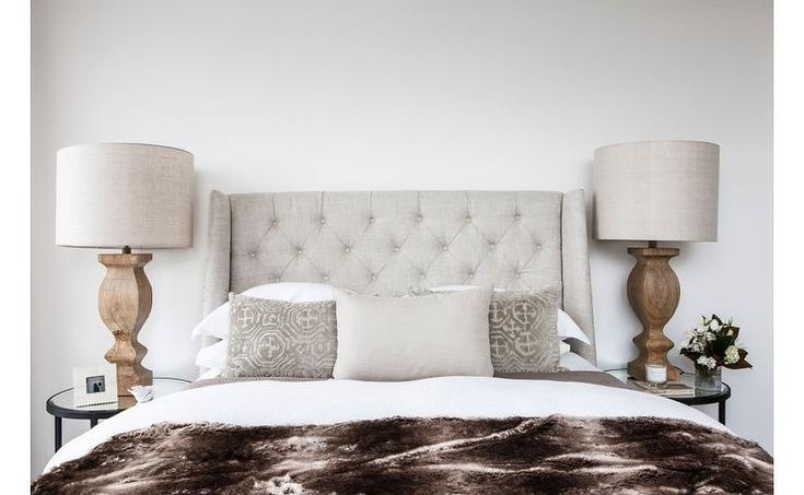Earth toned bedroom features a light grey tufted wingback headboard on bed dressed in white and - Spots of color in the bedroom linens and throws ...