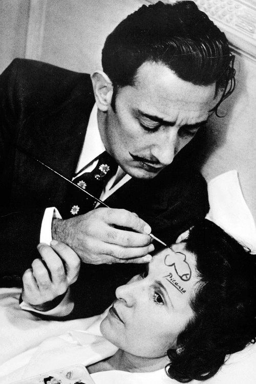 Salvador Dali drawing a penis on the forehead of a woman and signing it with…