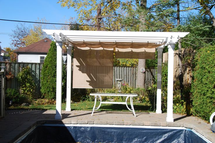 Colonial design white pergola with added Nesling Harmonica Shade and side Rollerblinds