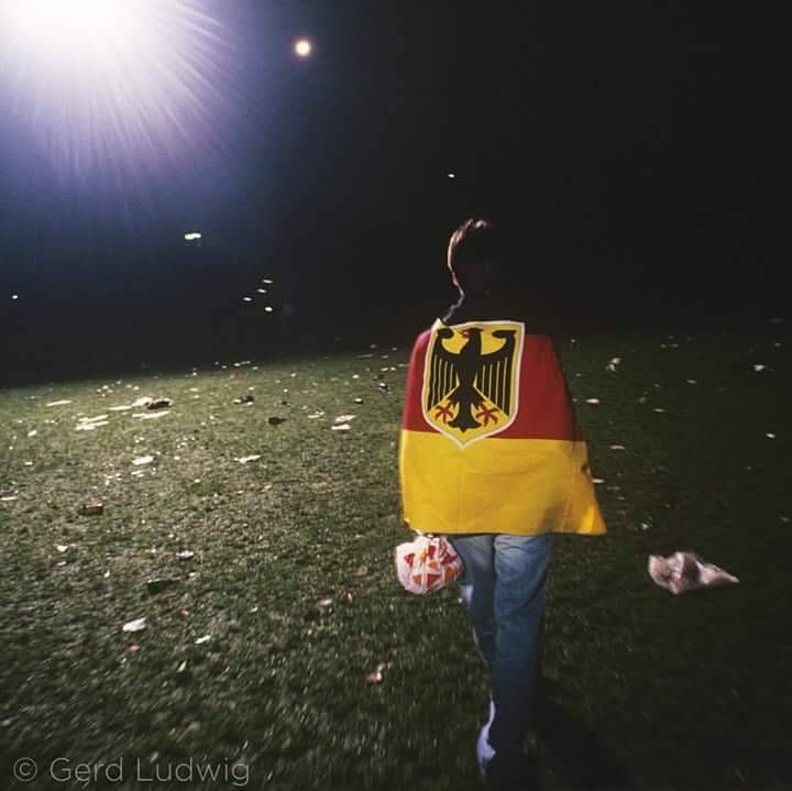 Photo by @GerdLudwig, shot in 1990 #onassignment for @natgeo. A lone reveler, still wrapped in the German flag, walks through the trash left following the celebration of German reunification.
