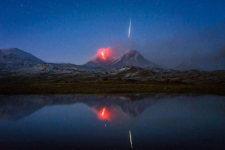 Un météore chute à côté d'un volcan en éruption