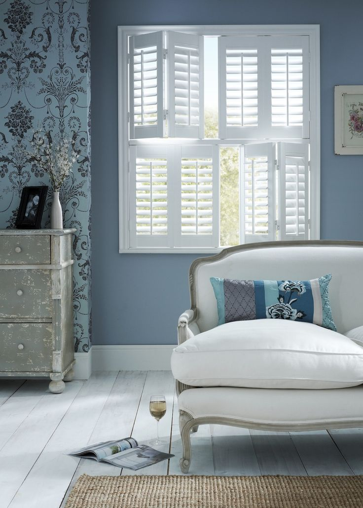 White Double Shutters by Apollo Blinds. White and blue home decor. Double shutters. Bedroom shutters. Modern window dressing.