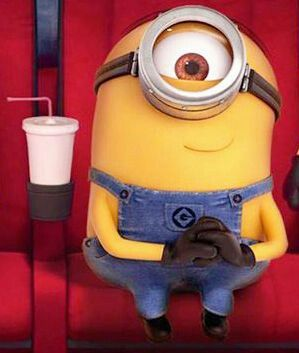 Minion sitting in movie theater with a drink in the cup holders