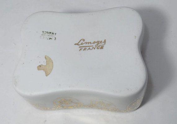 Ofrece es un vintage caja de la baratija de Limoges. Hecho de porcelana francesa, el cuadro firmado tiene un hermoso adorno rosa en la tapa. La caja está adornada con un filagree oro en los cuatro lados del exterior.  Medidas de caja de la baratija de TH 3 2 largo x 2 7/8 ancho x 1 1/2 alto. Una pieza muy agradable, alta calidad.  La porcelana está en muy buen estado con chips grietas ni rasguños.  Una adición maravillosa a la cómoda o tocador y un regalo pensativo para el coleccion...