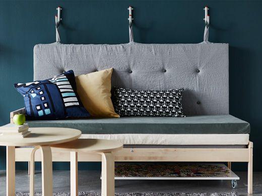 Sofa lavet af madrasser med et ryglæn, der hænger på kroge på væggen