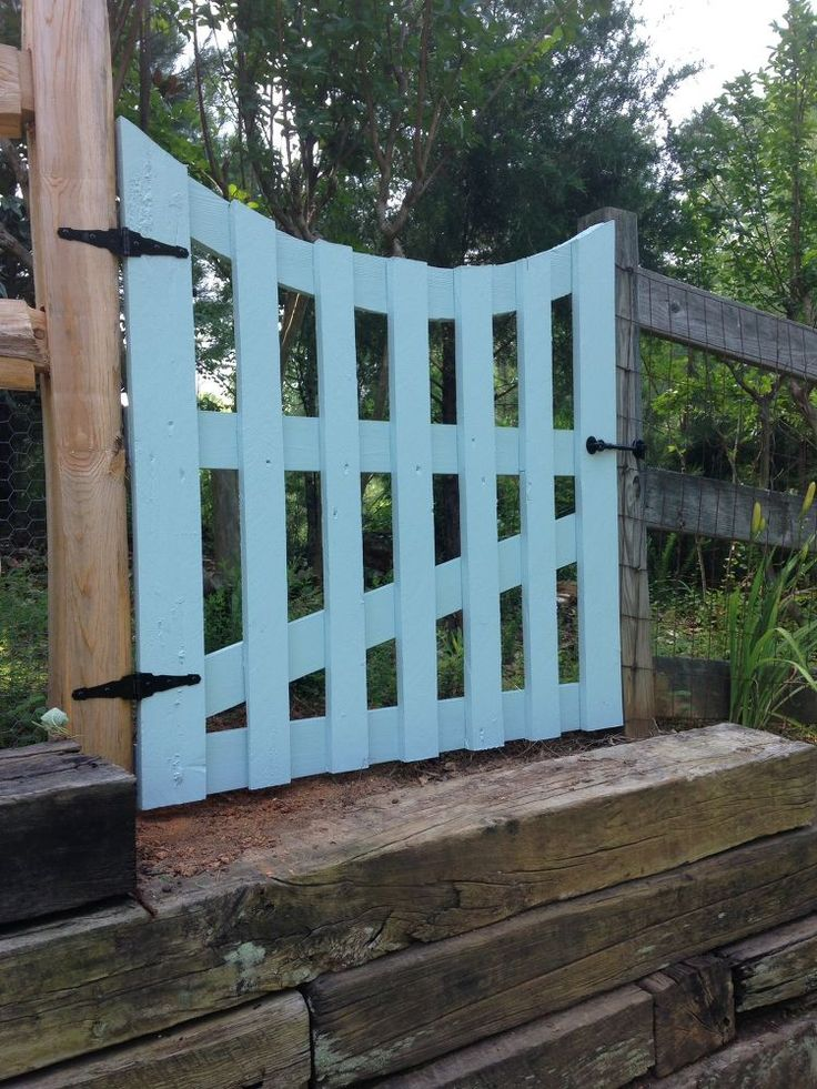 This pretty DIY garden gate is a mash up of an old pallet and what looks like a headboard that had seen much better days (cut and used to create the curved board at the top of the gate).