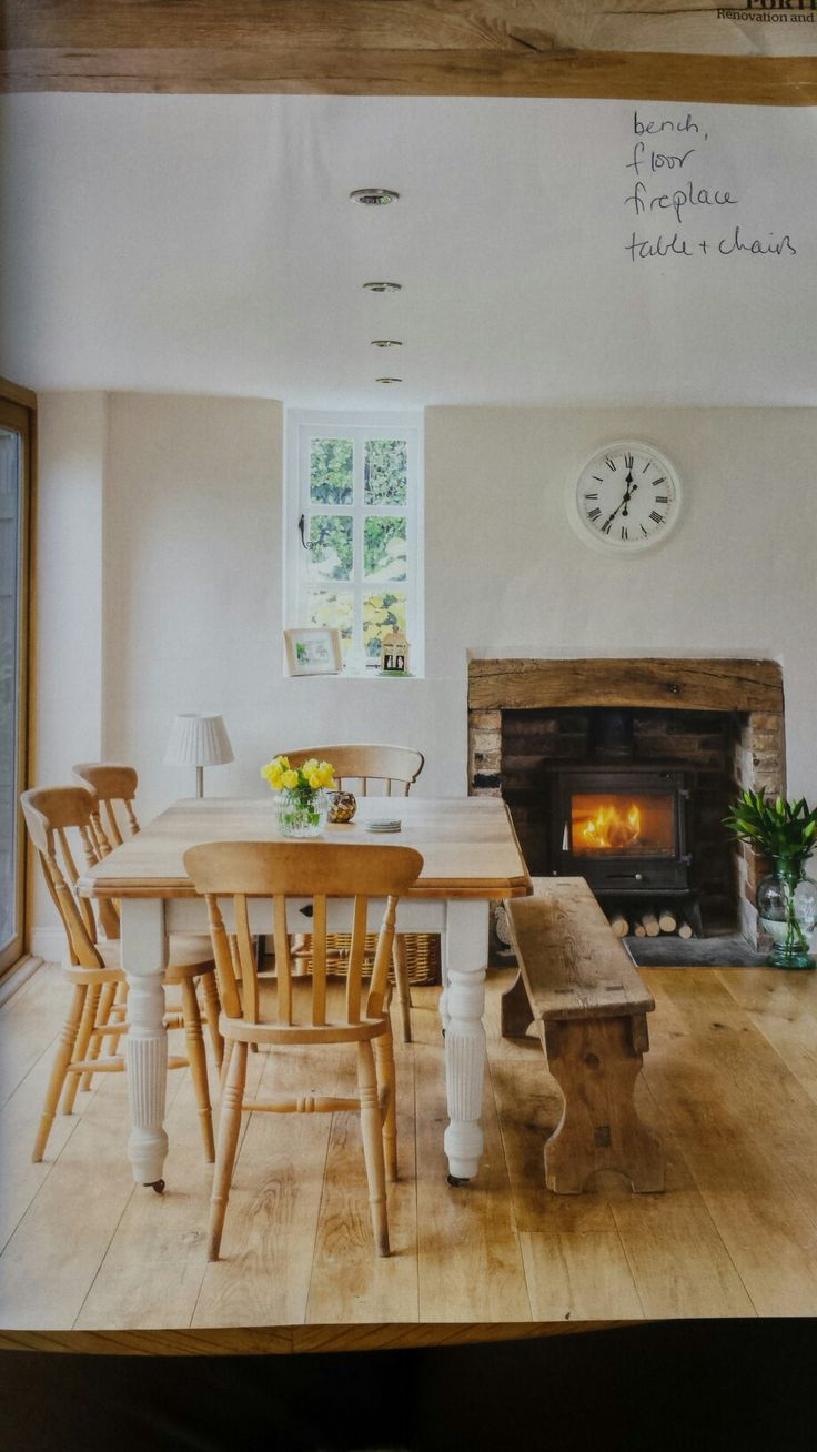 Rustic look of bench, wide floor boards, fireplace lintel, table and chairs