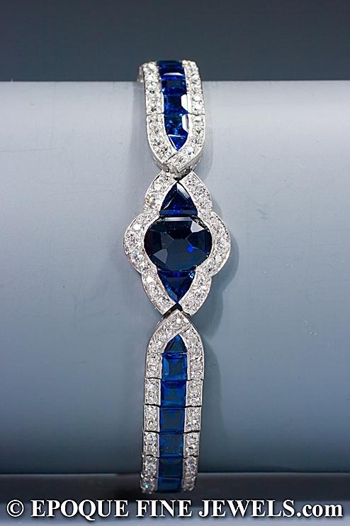 CHARLES HOLL  Un inusual Art Deco zafiro y un brazalete de diamantes,  engastado con zafiros Calibre de corte, bordeado por viejos diamantes de corte europeo, centrado por un óvalo cortado pesaje aprox zafiro. 2,50 ct, flanqueado por zafiros corte triangular, montado en platino y oro de 18 quilates. La montura está muy bien grabado en los lados. El óvalo de zafiro en el centro se fija al revés.  Circa 1925