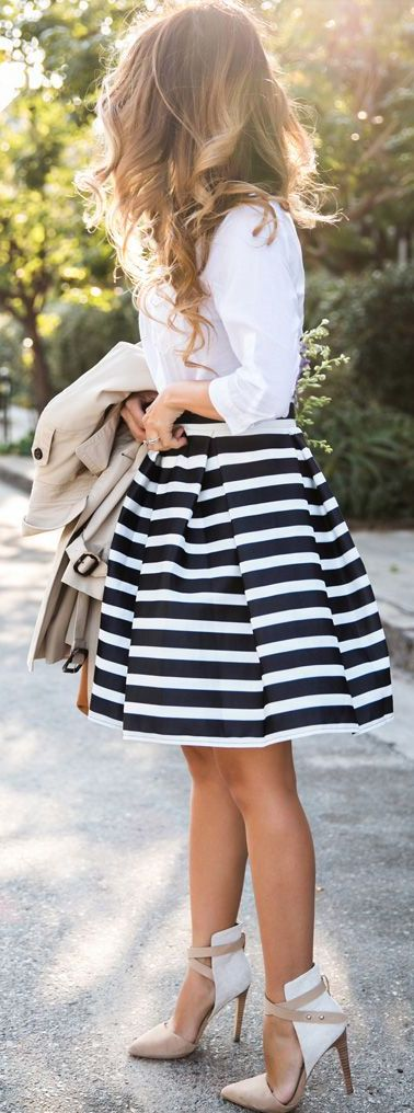 White blouse, blue and white striped midi skirt, tan and white strappy heels, and tan trench coat