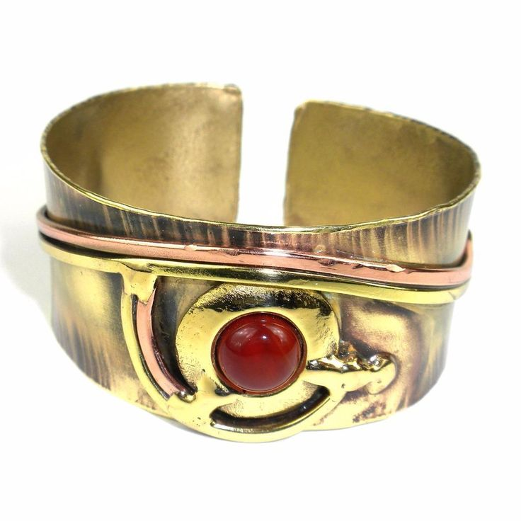 Handcrafted by South African artisans, this elegant 1-inch wide brass cuff is adorned with scrolls of polished copper and brass and finished with a carnelian stone. The feathering on the brass is achieved using high heat rather than paints or dyes.