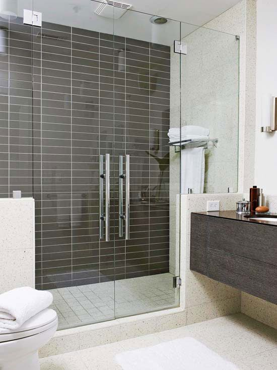 Cool Contrast - In this condo bathroom, frameless glass doors with statement-making handles and a mix of terrazzo and glass tiles cover the roomy shower from floor to ceiling.