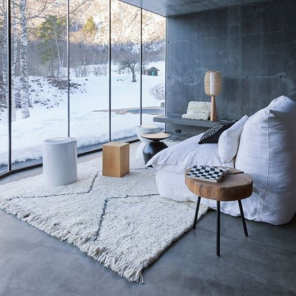 The Concrete walls and floor with full length windows convey an industrial look. The Plush rug and squishy seating turn it into a more relaxed and comfortable space whilst the timber elements add a warm, rustic feel.