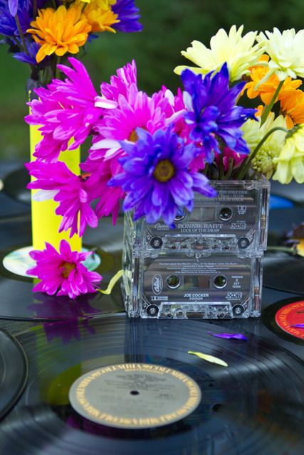 Decor for an 80's party: bright daisies in a clear glass square vase with cassette tapes = CENTER PIECES