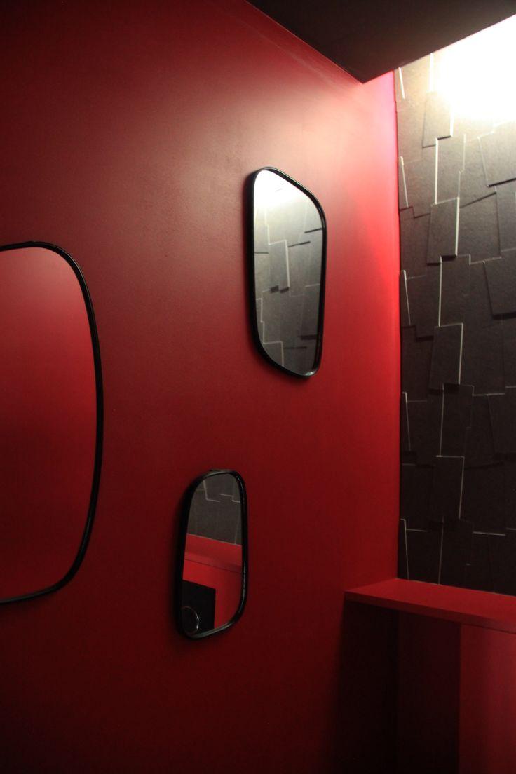 Travail de l'éclairage dans les WC avec une lumière indirecte tamisant les miroirs de forme organique ronde et les faïences puzzle 3D relief.