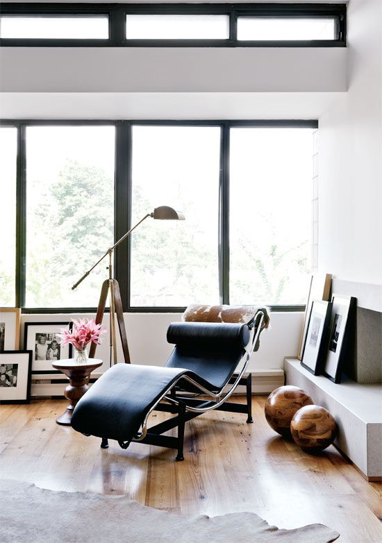 A high-end Mid-Century Modern Mies van der Rohe chair serves as both art and comfort in this living room.