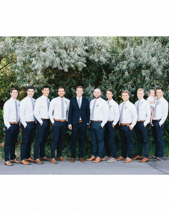 The groom chose a navy blue suit from H&M, a David Donahue shirt, a striped J.Crew tie, and Aldo shoes. He accessorized with a watch with a stained leather band and an ebony wood case made from ponderosa pine trees from his own line, Luno Wear. The groomsmen looked dapper in J.Crew pants and ties, white shirts, and brown shoes. As for the ring bearer, he wore a linen shirt and shorts from Four and Twenty Sailors with Salt Water Sandals.
