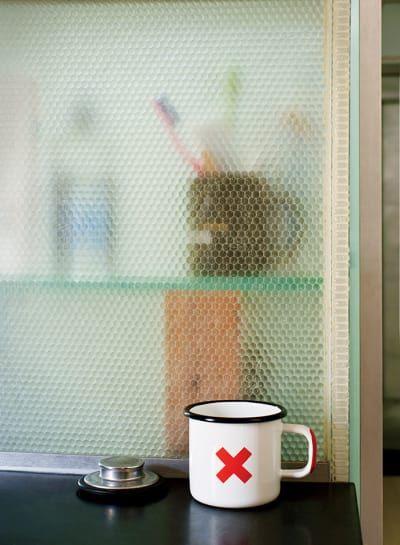 Esta cocina con paneles de salpicaduras hechos de panelite funciona también como una pared para el baño.