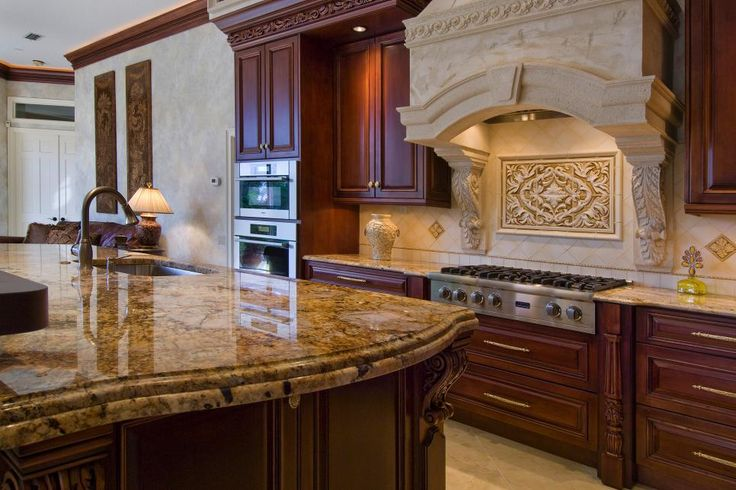 Gorgeous hood!  Rich wood cabinetry pairs with stunning granite countertops to create a sophisticated look in this Mediterranean-style kitchen. A cast stone range hood with a coordinating backsplash completes the classy design.