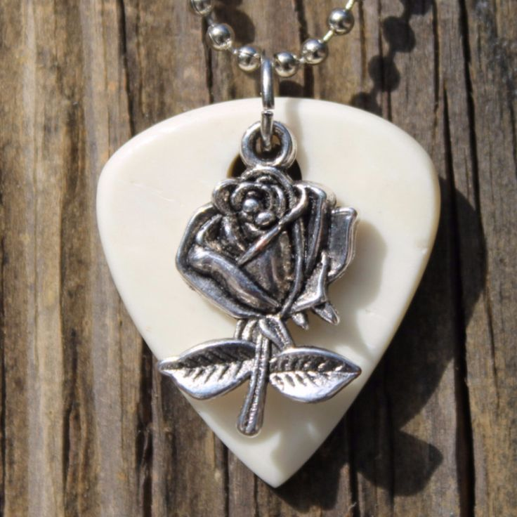 "Our Rose Guitar Pick Necklace is the ideal gift for guitar players, band members, and music lovers. Dangling from a silver-toned, 24"" ball chain necklace is a guitar pick of genuine cow bone. delicate"