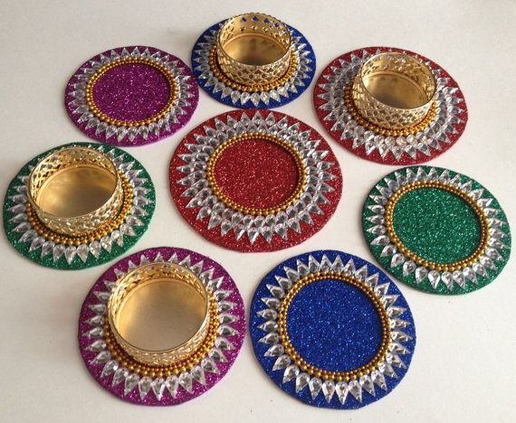 Tealight holder / diya and coasters.  You may buy the golden tealight holders seperately in variations or keep the tealights directly on the coasters.  Set contains(refer to the 2nd image),  (1) 2 center pieces with 2 lines of droplet shaped rhinestones are around 8-9cm each (2) 6 pieces with single line of droplet shaped rhinestones - 7-8cm each (3) 6 small flowers - 2.5cm each  With Tealight holders variations also contain, 8pcs of golden Tealight holders.  You can buy (1), (2) or (3)…
