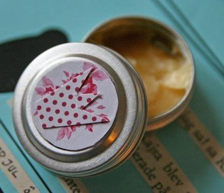 Ett återfuktande läppbalsam gör du av försvarets hudsalva (säljs på apoteket) mixat med honung i proportionerna 2/3 hudsalva och 1/3 honung (ej flytande) Blanda ordentligt med sked och värm eventuellt i ett vattenbad för att det ska smälta samman. Portionera sedan ut läppsmörjet i burkar och gör några fina ettiketter.