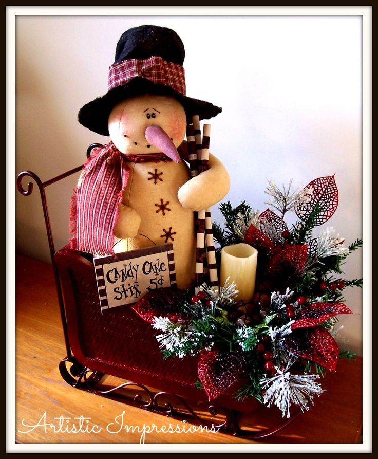 Large wood sleigh w/top hat snowman holding peppermint sticks & a prim sign. Embellished with frosted ming, lacquered berries, rusty jingle bells, glittery leaves & a wax coated flicker candle. $65