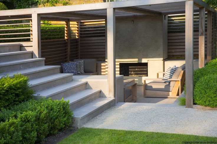 Formal structural garden . Contemporary timber pavilion, outdoor fireplace