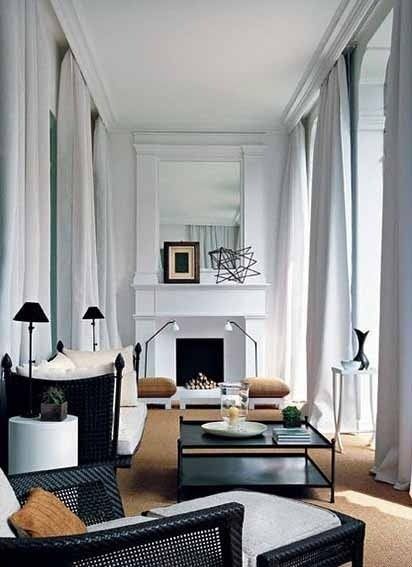 High ceilings, black and white color palette and classic furnishings make this long living room high on style.