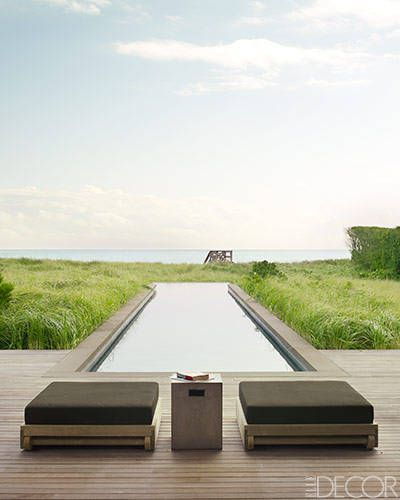Outdoor Spacen this Southampton home by Timothy Haynes and Kevin Roberts, teak ottomans by Sutherland with cushions in a Perennials fabric and a cement side table by CB2 sit beside the lap pool. The decking is ipe.
