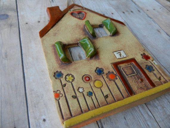 Questa casa carina era costruito a mano con lastra di argilla. Mentre largilla era ancora bagnato ho tagliato fuori dalle finestre e ha aggiunto la porta e tutti i piccoli dettagli.  Ho usato ossido di ferro lavare per evidenziare la struttura della casa. Esso è smaltata con smalti colorati.  Ho allegato una stringa di canapa per facile appeso alla parete. Farà un bel regalo per di qualcuno nuova casa.  Misure: circa H 5 1/2 x W 4  Tutte le mie ceramiche di compilazione mano ha la propria…