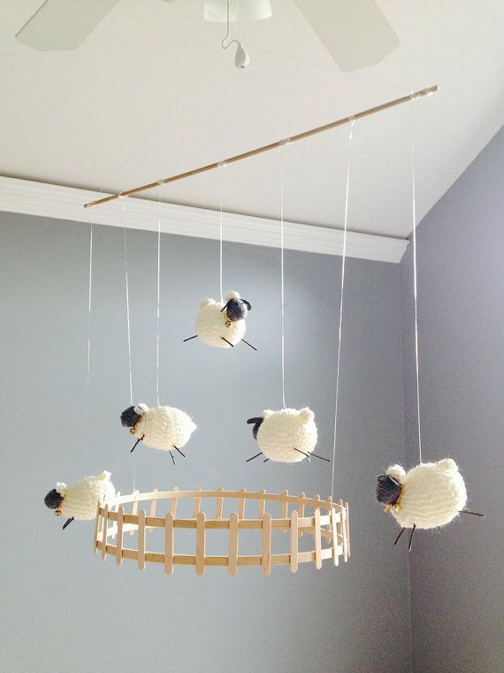 Five wooly lambs with bells jumping over pale wood fence bring serenity to the nursery or bedroom. Made of lightweight wood, the figures bob gently to lull your baby to sleep. Frame and fence are constructed of wood. Sheep are made of pure wool. Features five sheep with hand-made