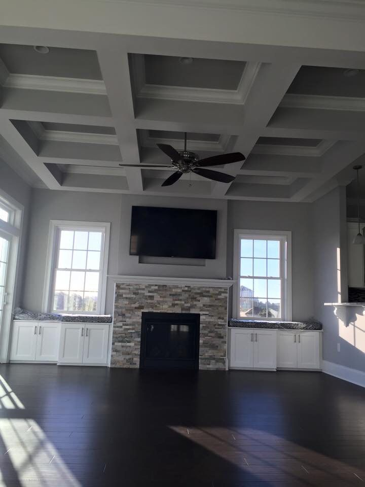 Gray living room with dark hardwood floors Stacked stone fireplace Coffered ceiling Window