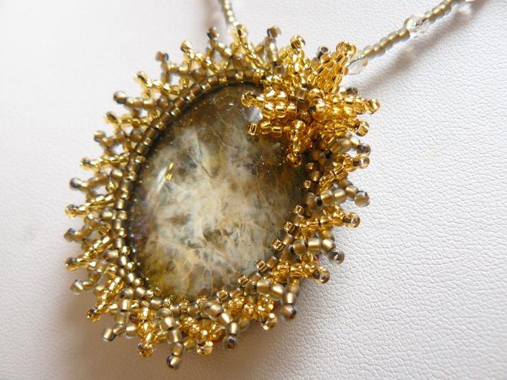 Misterioso Náhrdelník vytvořený technikou šitého šperku z korálků. Náhrdelník je vytvořen z obšitého sklěněného, ručně malovaného kabošonu z dílnyLileas materiál, v zlato-černo-bílé barvě. Kabošon je obšit kvalitním japonským TOHO rokajlem v hnědé se zlatým průtahem barvě s matnou úpravou a zlaté se stříbrným průtahem. Na dozdobení byl použit stejný ...