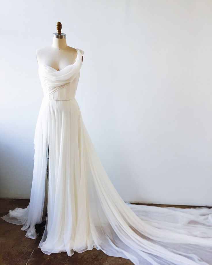 Artemisia gown.  Light and airy chiffon flowy wedding gown with asymmetrical off the shoulder, draped, sculptural bodice, and floaty skirt with lots of movement. Long train and front slit.  Designer runway wedding bridal dress