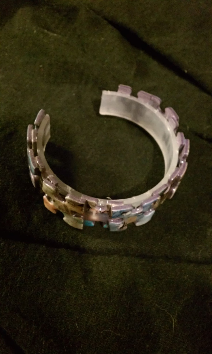 Plastic bangle styled bracelet. Maybe the jigsaw pieces could be personalised with pictures of the user's favourite things or even photographs. (DenverJewelryCompany, 2014)