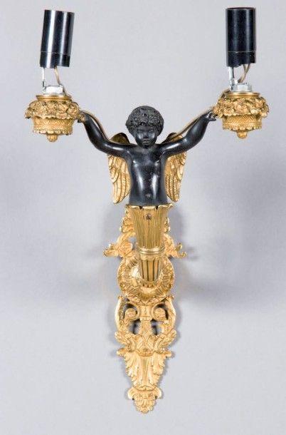 Applique en bronze doré et patiné noir à deux bras de lumière à décor d'un putto ailé sortant d'une corne d'abondance et soutenant à bout de bras des ...
