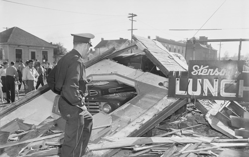 """""""Explosion Levels City Lunch Shop,"""" Officer inspects scene, Edmonton, AB, August 3, 1949"""