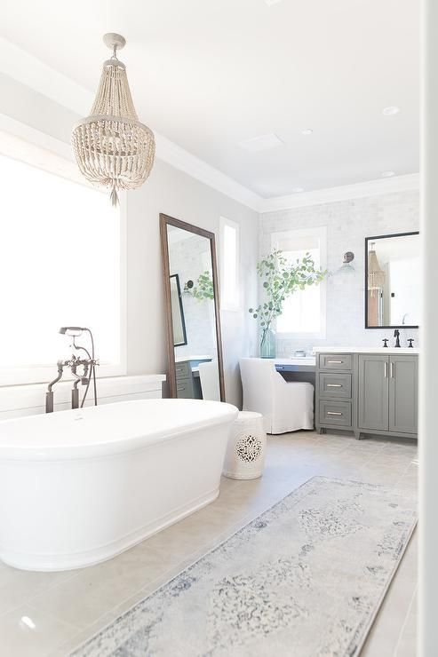 oval freestanding bathtub with a oil rubbed bronze vintage filler sits amidst an open concept bathroom design - Bathroom Designs With Freestanding Tubs